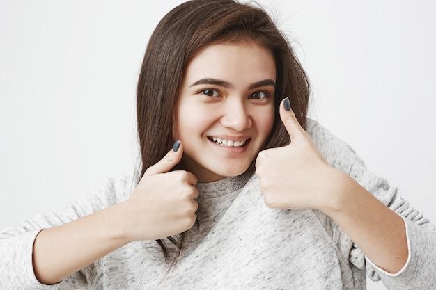 부드러운 귀여운 유럽 모델은 얼굴 근처에 엄지 손가락을 보이고 찾고있는 동안 크게 웃고