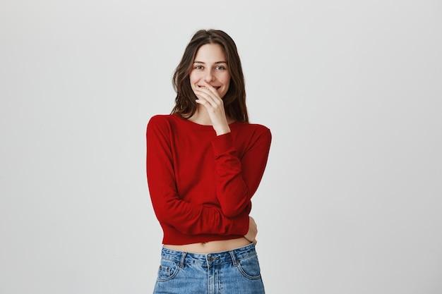 Нежная милая, улыбающаяся женщина прикрывает рот и смотрит в камеру