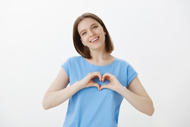Tenera donna carina che mostra il gesto del cuore, piace o ama qualcosa
