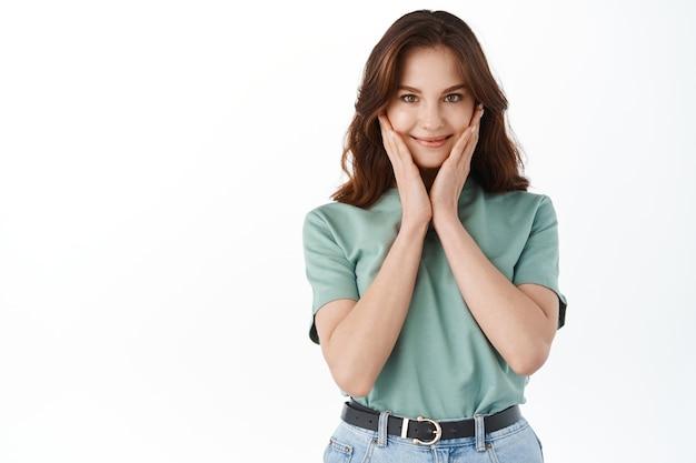 Tenera e carina giovane donna che arrossisce, sorride e tocca le guance, con un trucco nudo naturale, indossa una t-shirt estiva e un vestito di jeans, in piedi sul muro bianco