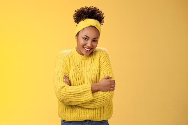 Tenera delicata giovane afro-americana allegra fidanzata riccia acconciatura maglione fascia che si abbraccia abbracciando felicemente sorridente fotocamera sentirsi morbida a proprio agio, in piedi sfondo giallo caldo.