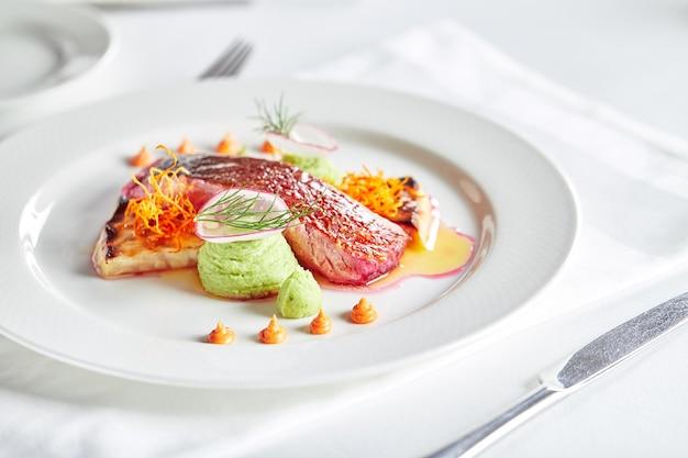 야채와 바질을 곁들인 부드러운 황새치 등심 연회 축제 요리