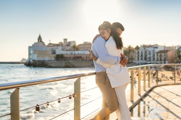 Tender ethnic couple embracing on embankment