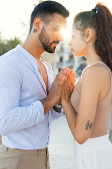 Tender ethnic couple touching hands