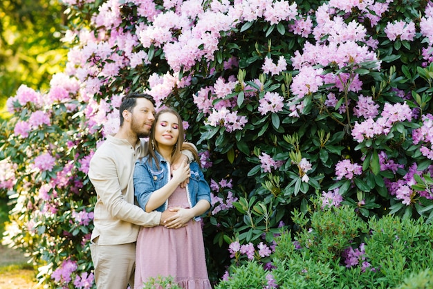 Tender feelings of love. a couple in love on a background of rhododendron flowers. beautiful girl enjoying spring flowers. the guy hugs her.