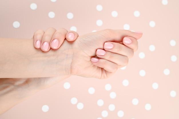 Нежные женские руки с обнаженными ногтями