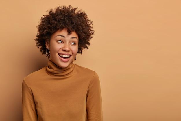 부드러운 여성은 기꺼이 옆으로 보이며 진심으로 웃으며 자연스러운 곱슬 머리를 가지고 있습니다.