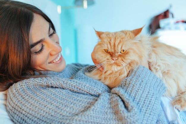 ベッドで彼女の猫をなでる優しい女性