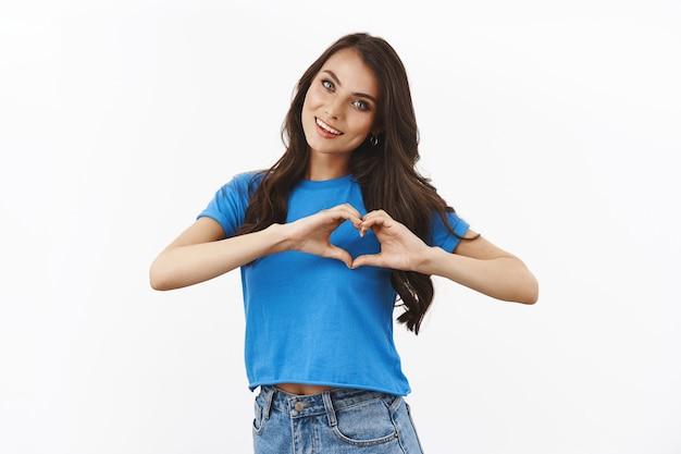 미소하고 심장 제스처를 보여주는 베이시안 블루 티셔츠를 입은 부드럽고 여성스러운 갈색 머리 여성