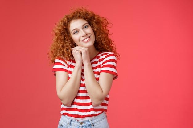 優しいフェミニンな思いやりのある赤毛の縮れ毛の女性のロマンチックな視線カメラは、頭の近くの手のひらを握り締めます愚かな素敵な表情笑顔で喜んで陽気な夢のようなため息をつきます。