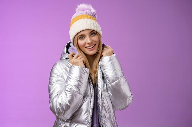 부드러운 여성 부드러운 금발 여자 친구 포즈 남자 친구 사진을 찍어 스키 리조트 휴가 입고 반짝이는 세련된 재킷 겨울 모자 서 기쁘게 보라색 배경 미소.