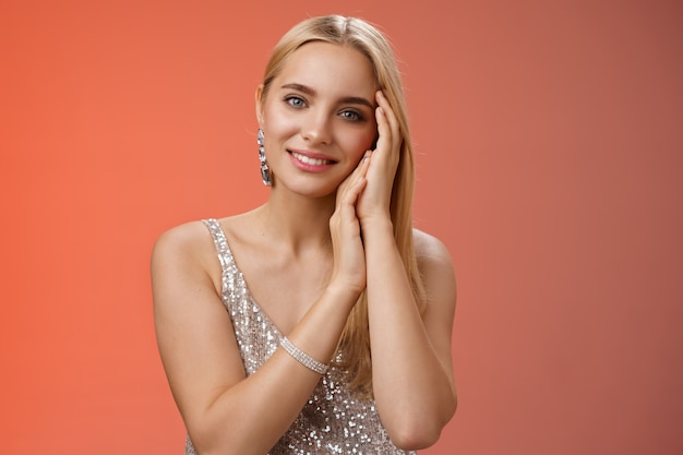 Tender feminine gentle blond woman in silver stylish dress touching face lovely smiling
