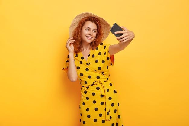 Tender feminine girl with ginger hair, takes selfie on smartphone, smiles broadly