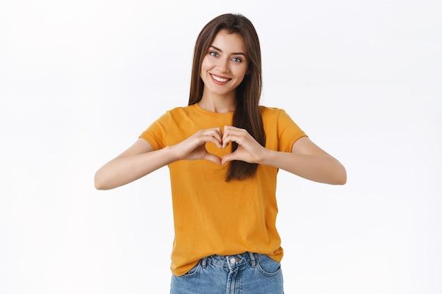 黄色のtシャツを着た、優しくてフェミニンな格好良いブルネットの女性、ハートまたは愛のサインを示し、笑顔、愛情、愛情を表現し、ロマンスと喜びに満ち、白い背景にうれしそうに立っています