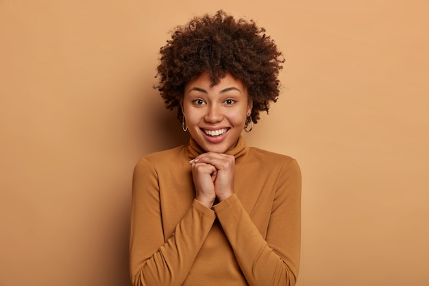 Tender feminine woman has curly hairstyle, gazes sincere at camera, holds hands together under chin, wears casual brown turtleneck