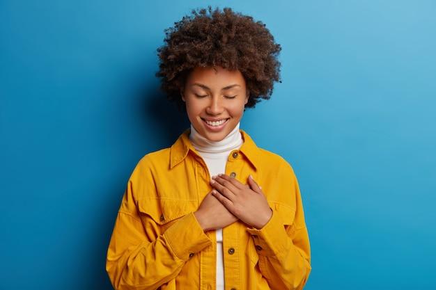 Нежная женственная женщина держит руки на сердце, имеет благодарный вид, ценит усилия, с закрытыми глазами, носит желтую рубашку, изолированную на синем фоне
