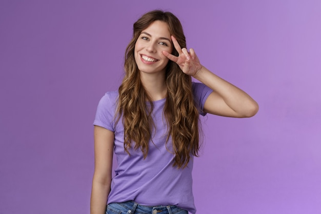 Tender friendly outgoing attractive female tilt head lovely cute gaze show peace victory sign express positivity love cherish friendship stand purple background upbeat relaxed casual pose