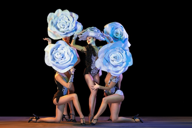 Tender garden. young female dancers with huge floral hats in neon light on black wall.