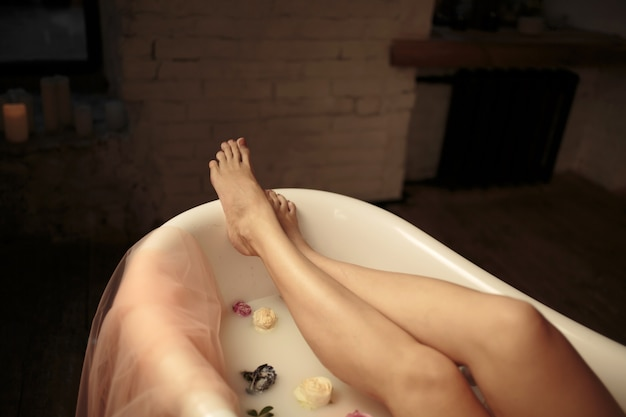 Tender girl enjoys a bath with milk and roses. view of the feet in the bathroom