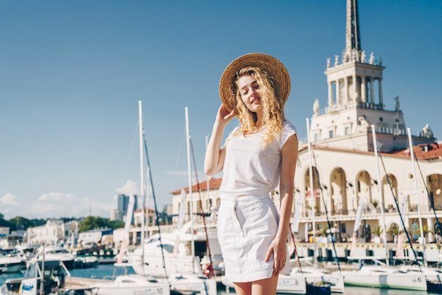Tender girl in white clothes, covers her eyes from the sun against the background of the sea terminal and ship masts