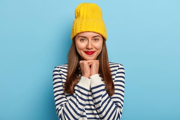 부드러운 좋은 찾고 어두운 머리 여자는 노란색 모자와 줄무늬 스웨터에 파란색 배경에 서, 빨간 립스틱을 착용