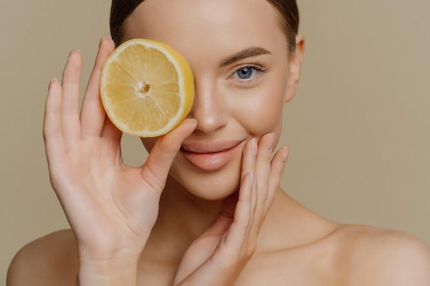 Нежная симпатичная женщина держит над глазом ломтик свежего лимона и рекомендует органическую косметику
