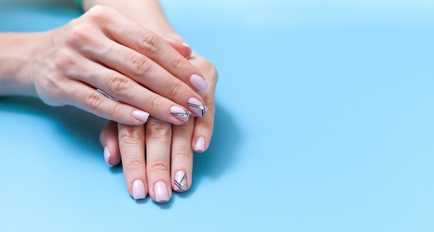 Tender hands with perfect nude manicure on pastel blue