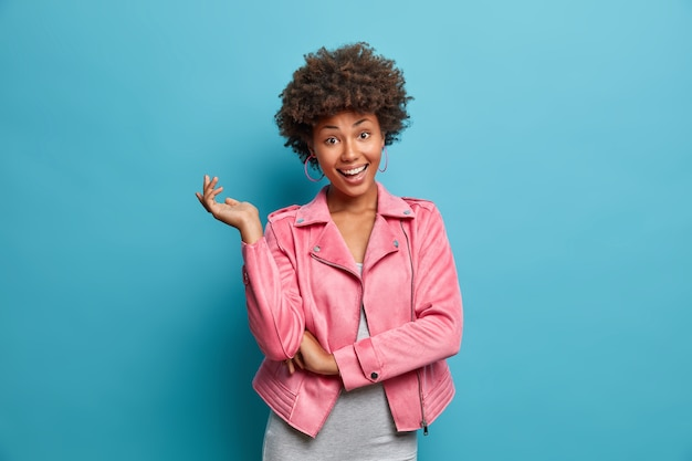 Tender happy young african american woman in pink jacket raises hand, shows perfect white teeth, rejoices good news, has curly hair, poses