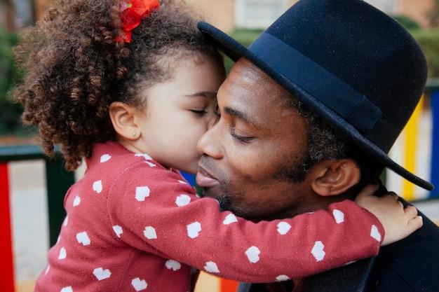 Tender hug between hispanic father and daughter