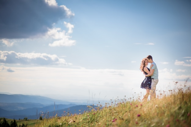 Tender hugs of a couple standing on a green hill before gorgeous landscape