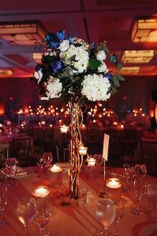 Tenero centrotavola di ortensia sulla tavola rotonda con candele