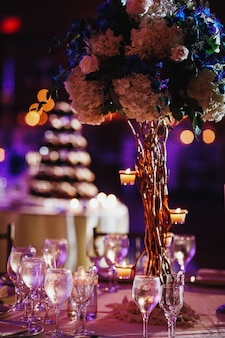 Tender hydrangea centerpiece and wine glasses on blurred background