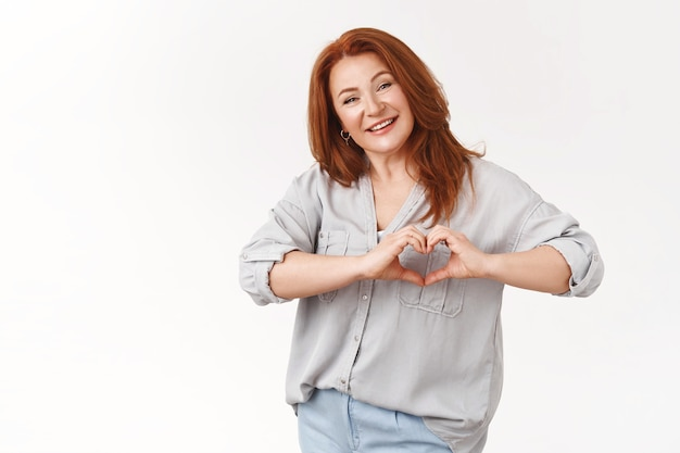 Tender joyful charismatic middle-aged 50s redhead elegant woman smiling delighted happiness show love sign chest express sympathy cherish relationship, standing white wall