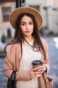 Tenera signora che cammina lungo la strada con borsetta e tazza di caffè.