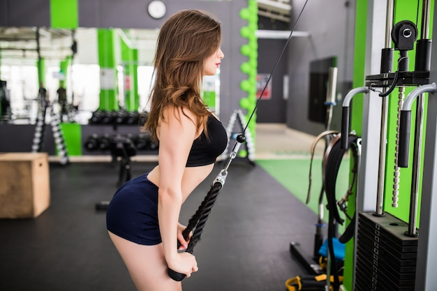 Tender lady with strong fit body make exercises in gym with sport simulator