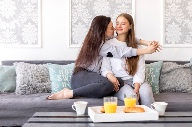 Tender lesbian couple sitting on sofa with breakfast
