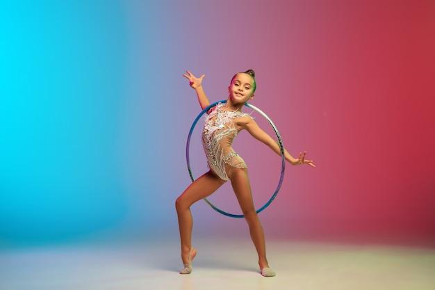 入札。小さな白人の女の子、リズミカルな体操選手のトレーニング、ネオンのグラデーション青赤スタジオの背景に分離して実行します。優雅で柔軟な、強い子供。スポーツ、モーション、アクションの概念。