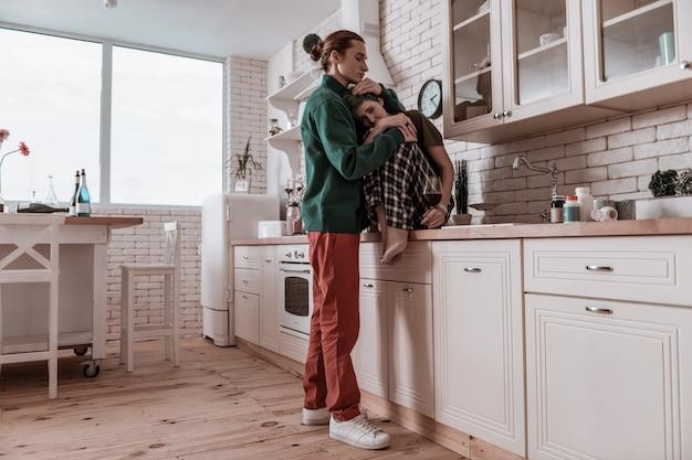 Нежная маленькая девочка. любящий парень в красных штанах обнимает свою нежную маленькую девочку, чувствуя стресс