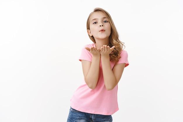 Нежная милая кавказская белокурая девушка в розовой футболке дует воздушный поцелуй руками возле надутых губ, глупо улыбается, посылает любовь, признается в сочувствии, стоя на белой стене, оптимистично