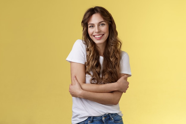 Tender lovely happy good-looking girl long curly hair hug herself wanna warm cuddles smiling toothy pleased friendly conversation having fun wear white t-shirt embracing own body yellow background