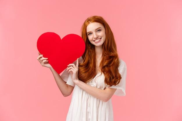 하얀 드레스를 입고 부드러운 사랑스러운 빨간 머리 백인 여성, 큰 붉은 마음을 잡고 웃고, 고백 사랑, 동정심 또는 감탄,