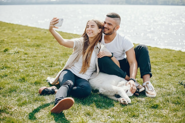 Tender and merry lovers are having a good time at the lake with dog