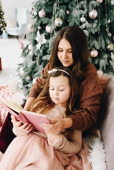Tender mom and daughter moment with book near decorated christmas tree