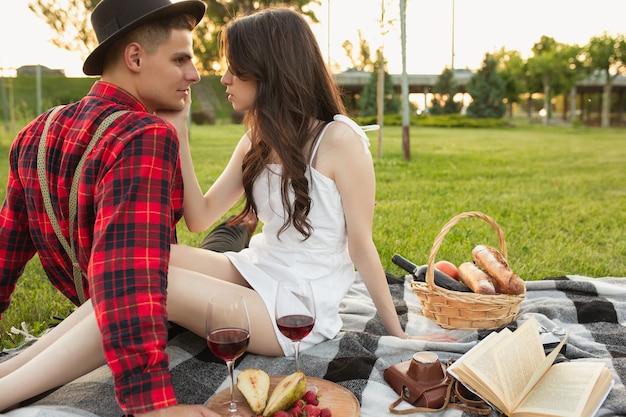 부드러운 순간. 여름날 공원에서 함께 주말을 즐기는 백인 젊은 부부. 사랑스럽고 행복하고 쾌활해 보입니다. 사랑, 관계, 웰빙, 라이프 스타일의 개념. 진심어린 감정.