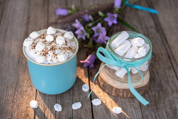 Tender morning milk drink with foam and marshmallows in a blue cup on a wooden space.