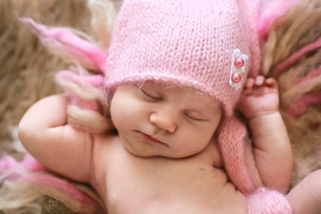 Tender newborn baby in pink cap sleeps stretching