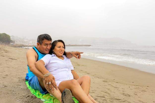 해변의 모래에 앉아 사랑에 빠진 부드러운 나이 든 민족 커플