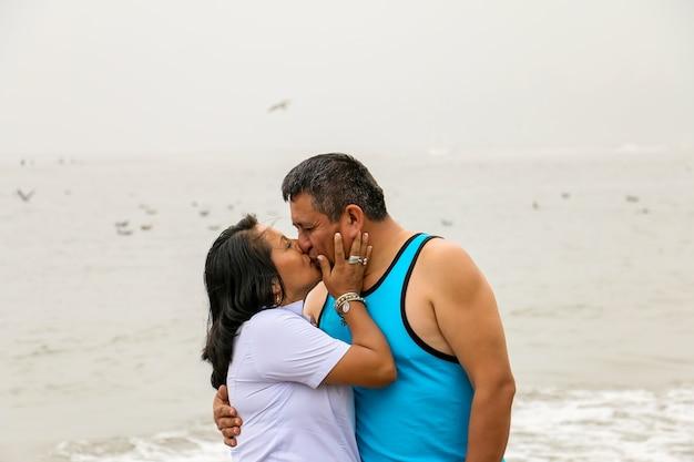 해변 옆에 서 있는 사랑에 빠진 부드러운 나이 든 민족 커플