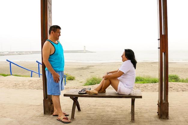 바다 앞에 앉아 사랑에 빠진 서로를 바라보는 부드러운 나이 든 민족 커플
