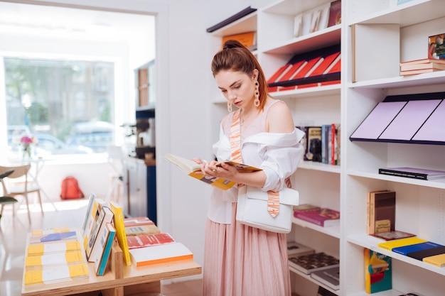 Нежный наряд. симпатичный женский человек, склонивший голову во время чтения текста